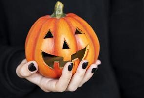 mains féminines tenant des citrouilles drôles sur fond noir photo