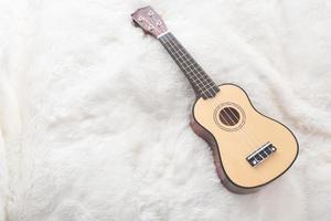 petite guitare sur laine blanche photo