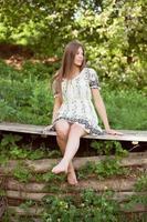 belle fille est assise sur les planches photo