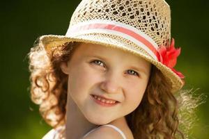 petite fille bouclée heureuse dans un chapeau photo