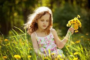 fille rassemble un bouquet de pissenlits photo