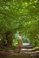 fille debout au milieu de la journée d'été de la ruelle verte photo