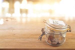 boîte à pourboires, pièce de monnaie dans le bocal en verre au café devant le miroir la nuit photo
