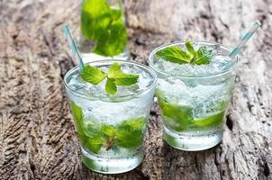 verre d'eau froide avec des feuilles de menthe fraîche et des glaçons photo