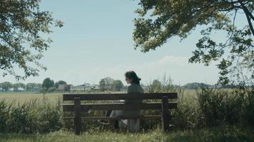 femme s'assoit sur un banc en bois dans le pays et commence à lire un livre photo