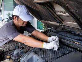 mécanicien tenant une poignée de clé à molette tout en réparant une voiture. photo