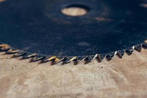 scie circulaire à lame ronde sur le fond de la table en bois photo