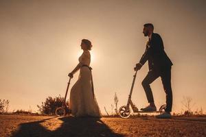Couple de mariage silhouette chevauchant un scooter le long de la route au coucher du soleil photo