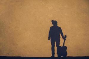 Ombre et silhouette de l'homme avec un fond de guitare de mur de béton photo
