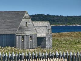 une vieille maison en bois dans un champ de fleurs blanches au bord du lac photo