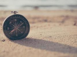 la boussole est placée sur la plage et le soleil au coucher du soleil du soir photo
