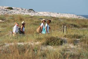 Les touristes à vélo sur la plage des illetes à Formentera en Espagne photo