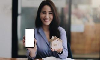 agent immobilier montrant un modèle de maison avec un écran blanc vierge photo