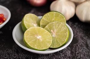 citron vert à moitié coupé dans une tasse blanche sur ciment noir. photo