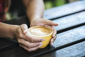 mains de femme tenant une tasse de café au café photo