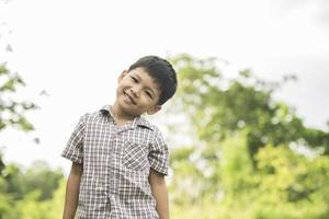 portrait de petit garçon debout dans le parc naturel souriant à la caméra. photo