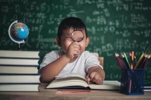 enfant observant ou étudiant un modèle de globe éducatif en classe. photo