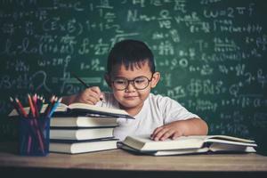 garçon écrit un livre en classe. photo