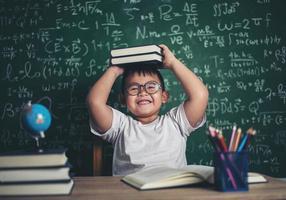 garçon avec des livres assis dans la salle de classe photo