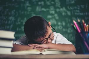 garçon dormant sur les livres dans la classe. photo