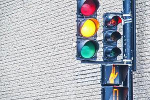 Trois poteaux de feux de circulation colorés à côté d'un bloc de briques dans la ville photo