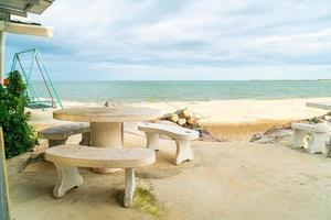 table et chaise extérieure de patio sur la plage avec le fond de plage de mer photo