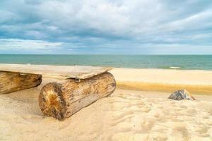 banc en bois sur la plage avec fond de plage de la mer photo