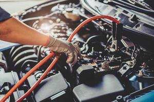 mécanicien automobile tenant le cavalier de câbles à travers l'électricité de la batterie photo