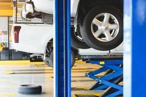 Voiture de ramassage soulevée sur l'ascenseur de voiture dans le pneu du centre de garage de service automobile photo