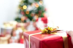 main tenant le cadeau dans l'événement du jour de noël. fête de noël et nouvel an photo