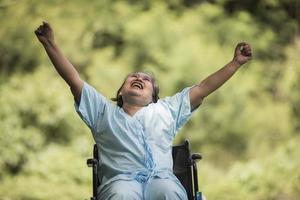 Femme âgée solitaire assise sur un fauteuil roulant au jardin à l'hôpital photo