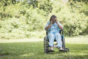 Femme âgée seule assise triste sentiment sur fauteuil roulant au jardin photo