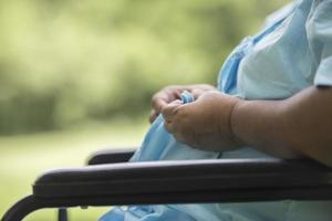 Close up femme âgée solitaire assis sur un fauteuil roulant au jardin photo