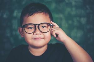 petit garçon réfléchi avec un livre près d'une commission scolaire photo