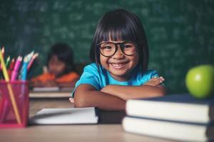 portrait d'écolière souriante assise à la table avec des livres photo