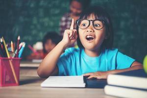 petite fille réfléchie avec un livre près d'une commission scolaire photo
