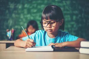 fille avec dessin au crayon à la leçon en classe photo