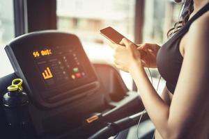 femme asiatique utilisant un téléphone intelligent lors de l'entraînement ou de la musculation photo