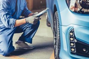 technicien mécanicien automobile asiatique tenant le presse-papiers vérifiant l'entretien photo