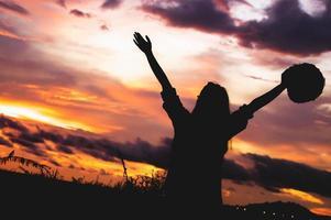 silhouette de femme heureuse bras ouverts sous le lever du soleil au bord de la mer photo