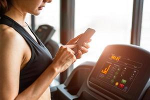 femme utilisant un téléphone intelligent lors de l'entraînement ou de la musculation photo