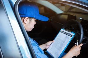 mécanicien tenant le presse-papiers et vérifiant l'intérieur de la voiture pour l'entretien photo