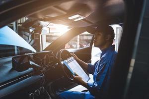 mécanicien tenant le presse-papiers et vérifiant à l'intérieur de la voiture photo
