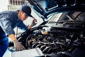 technicien mécanicien automobile tenant une lampe de poche vérifiant le moteur photo