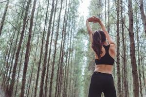 femmes étirant les bras et respirant l'air frais au milieu de la pinède photo