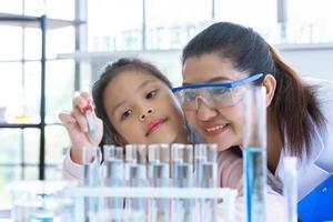 fille scientifique et enseignant laissant tomber la pipette liquide de substance de solution photo