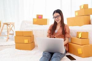 femme asiatique de beauté utilisant un ordinateur portable pour le support client dans la chambre photo