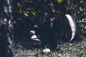 démon sorcier assis et tenant reaper photo
