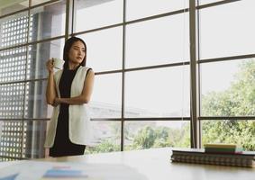 jeune femme d'affaires asiatique prenant une pause pour boire du café photo