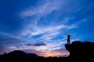 silhouette d'un homme sur le rocher au coucher du soleil photo